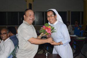 Mr. Robi Christopher D'Costa receiving gifts from Sr. Nisha Gagra