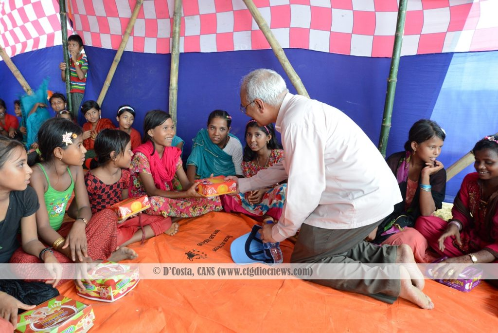Archbishop Moses M. Costa CSC is sharing meal with a Rohingya Child.