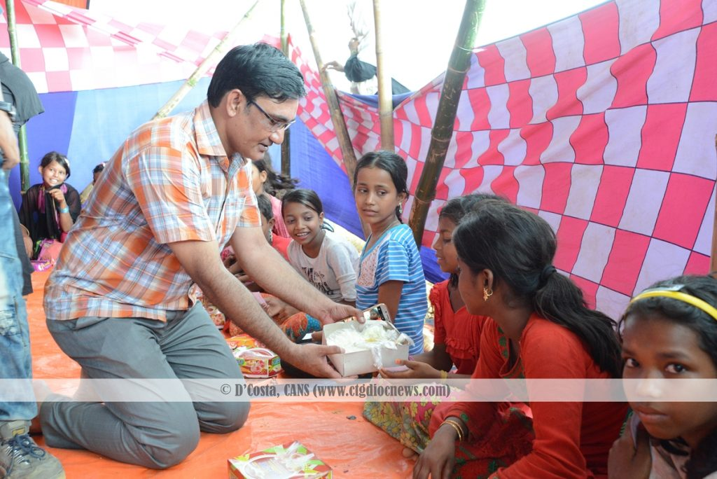 Regional Director of Caritas Chittagong James Gomes is sharing meal with a Rohingya Child