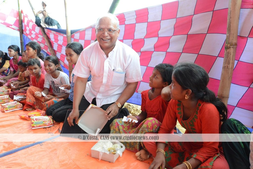 Bishop Lawrence S. Howlader CSC is sharing meal with a Rohingya Child