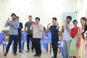 Participants performing action songs along with resource person